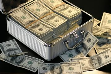 A metal box filled with cash on a table surrounded by more bills.
