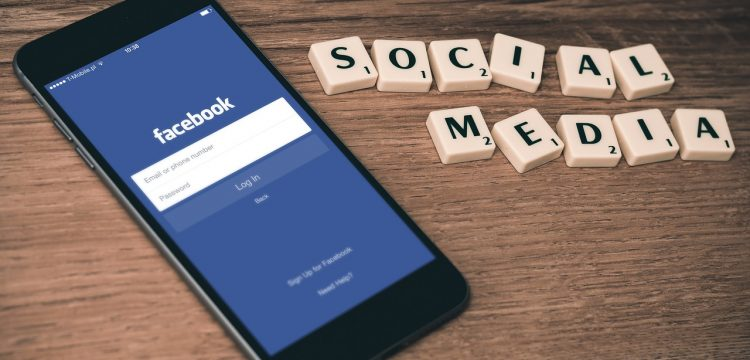 """A cell phone lying on a table with the words """"Social Media"""" spelled out in Scrabble letters."""