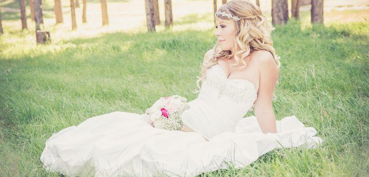 Bride with a bouquet lying on the grass.