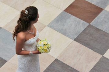A bride holding a yellow bouquet, looking over her shoulder.