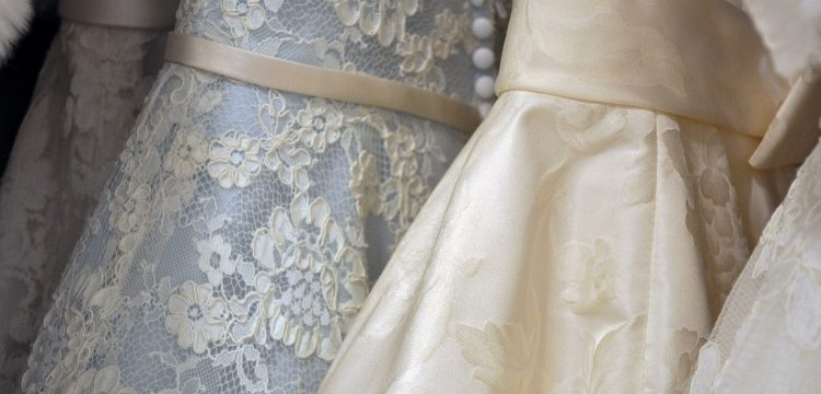 A row of hanging wedding gowns.