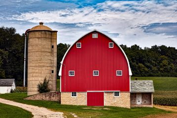 A red barn with a sloped roof next to a silo.