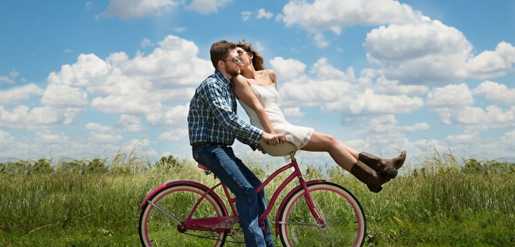 Engaged couple riding a bicycle.