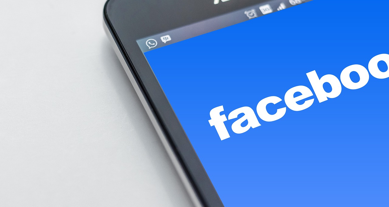 Cell phone with Facebook logo on it.