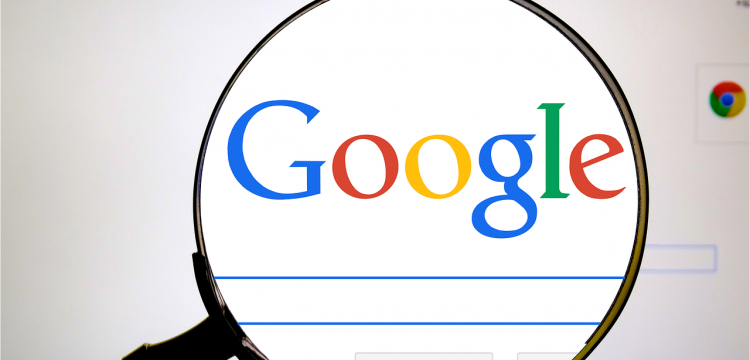 A magnifying glass focusing on the Google logo on a computer screen.