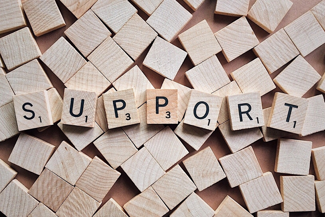 """Scrabble board spelling out, """"Support""""."""