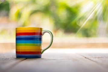 A rainbow mug with the sun shining down on it.