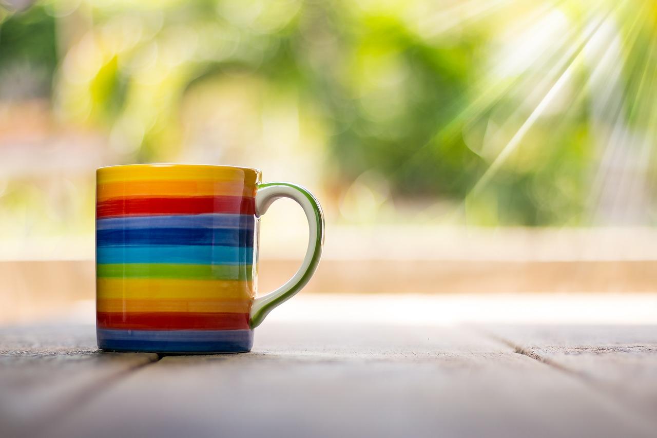 A rainbow mug with the sun shining down on it.