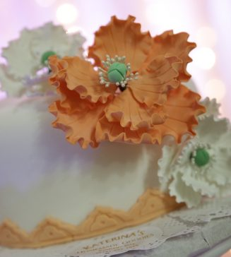 A close up of a wedding cake with a large orange icing flower on it.