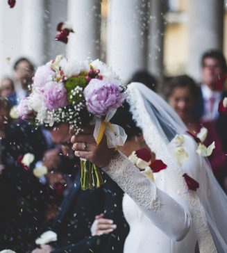 Flowers falling upon bride and groom outside their church.