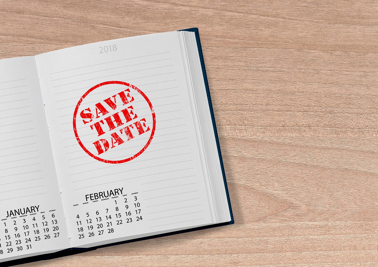 "A book opened to a page that reads, ""Save the Date""."