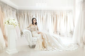 Bride in a dress sitting on a chair in an all white room.