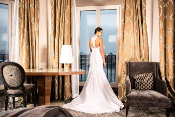 Woman wearing wedding dress in an elegant room, looking out a window.