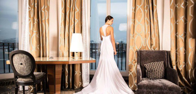 Woman wearing wedding dress in an elegant room, looking out a window.