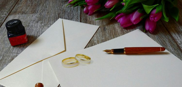 Wedding invitations with two wedding bands sitting on them.