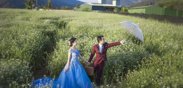 A bride and groom standing in a field with the groom holding an umbrella.