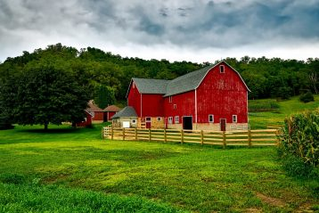 A beautiful red barn in a green pasture.