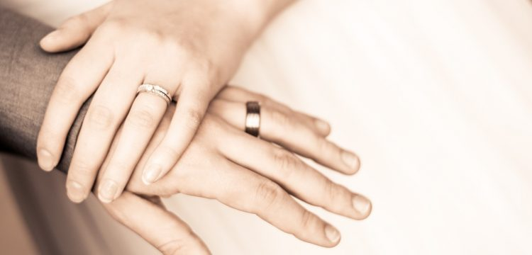 A bride's hand overlapping her groom's.