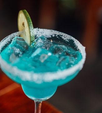A blue cocktail with a slice of lime in it.