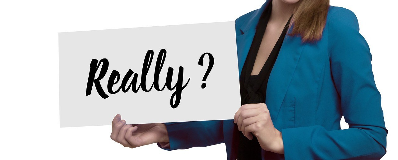 "A businesswoman holding a large board with the word ""Really?"" on it."