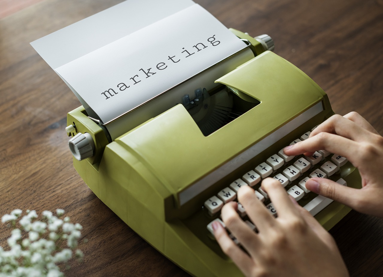 """A typewriter with a paper in it with the word """"marketing"""" typed on it."""