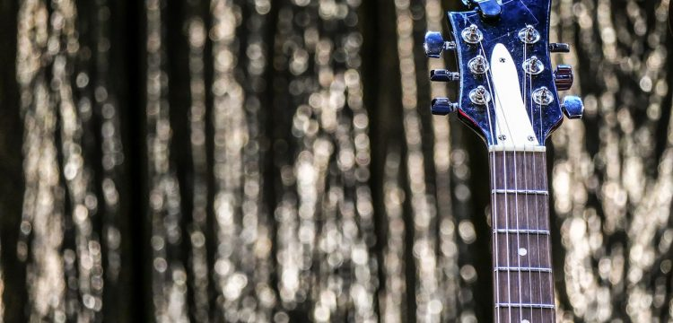 The top part of a guitar with strands of glitter behind it.