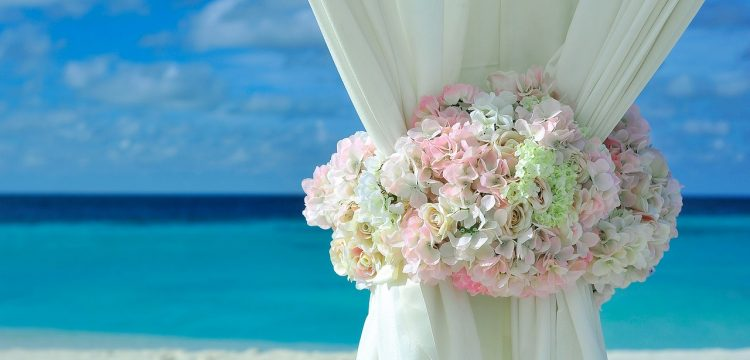 Wedding decor indicative of a beach wedding with an ocean view behind it.