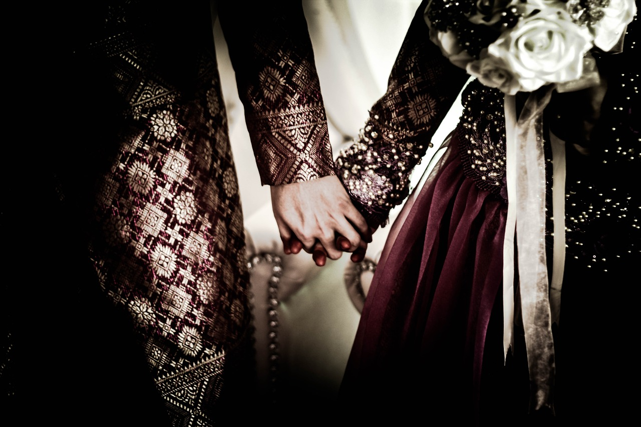 A medieval couple holding hands in their wedding finery.