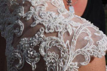 An intricately beaded lace shoulder of a bridal gown.
