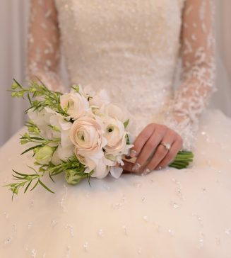 A torso view of a bride wearing a long sleeved wedding gown.