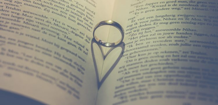 Wedding ring standing upright in a book with its shadow in the shape of a heart.