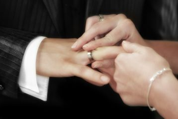 A woman putting a wedding band on a man's hand.