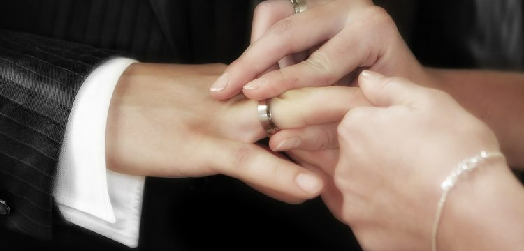 Woman wearing a wedding band putting a ring on a man's hand.