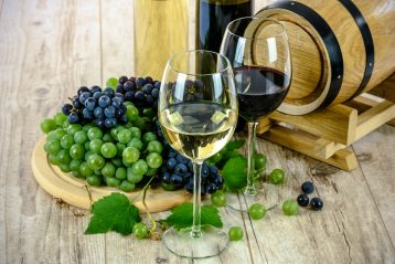 Two wine glasses on a table surrounded by grapes.