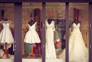 Mannequins outfitted in bridal gowns in a shop window.