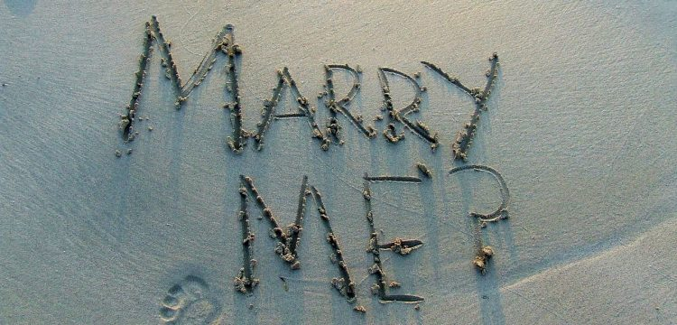"""Marry Me?"" written on a beach."