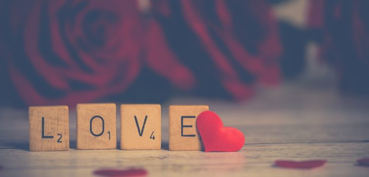 """Scrabble letters spelling out """"love"""" with a small red heart on the side."""