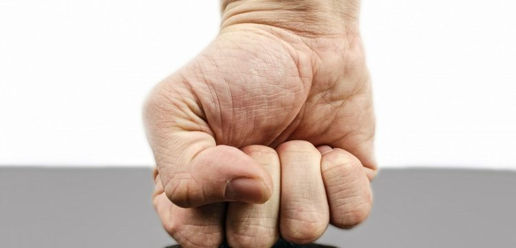 A man's fist hitting a table.