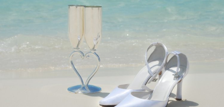 Glasses of champagne and wedding shoes on a beach.