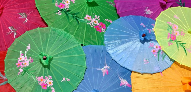A bunch of overlapping colorful Japanese parasols.