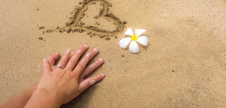 A heart drawn in the sand with a man and a woman's interlaced hands by it.