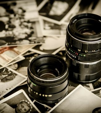 Two camera lenses surrounded by photographs.