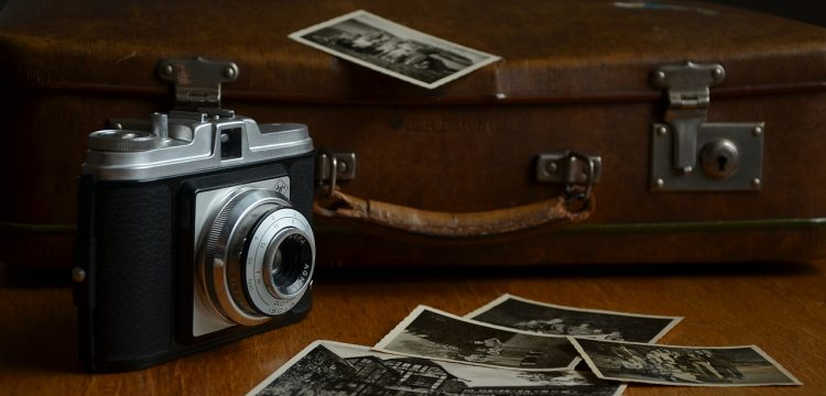 An old camera and suitcase with photos scattered about.