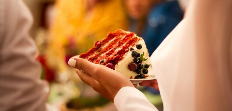 A woman holding a piece of red velvet cake.
