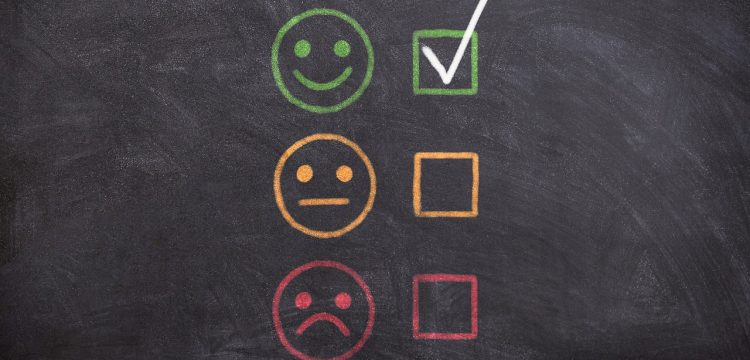 """Three smiley faces indicating """"good"""", """"neutral"""", and """"bad"""" with a check on the """"good"""" one."""