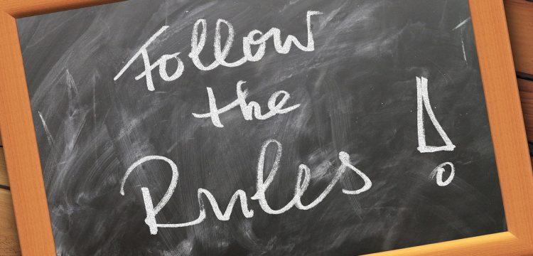 "A blackboard that reads, ""Follow the Rules""."