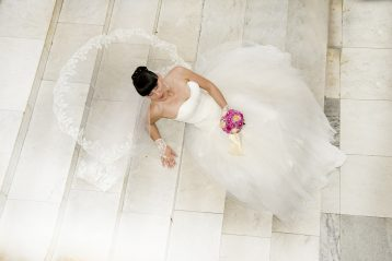 Model with wedding dress lying on white steps.
