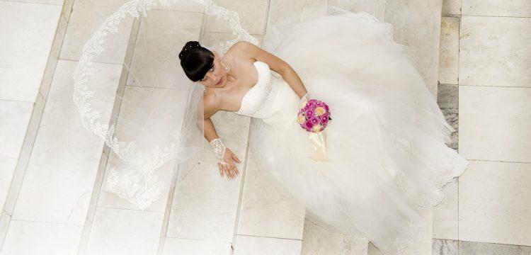 Model with wedding dress lying on white steps.