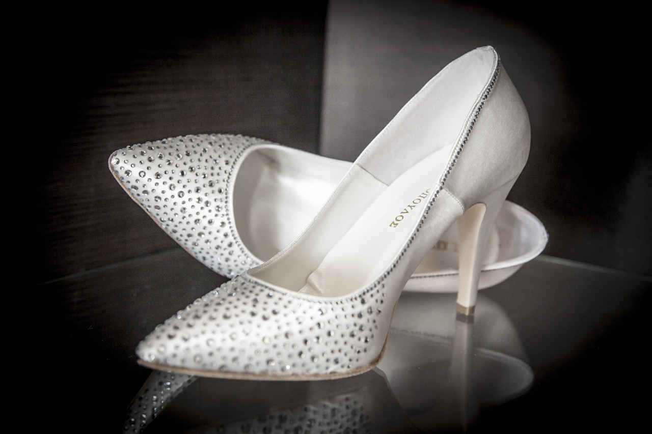 A pair of white sparkly bridal pumps.
