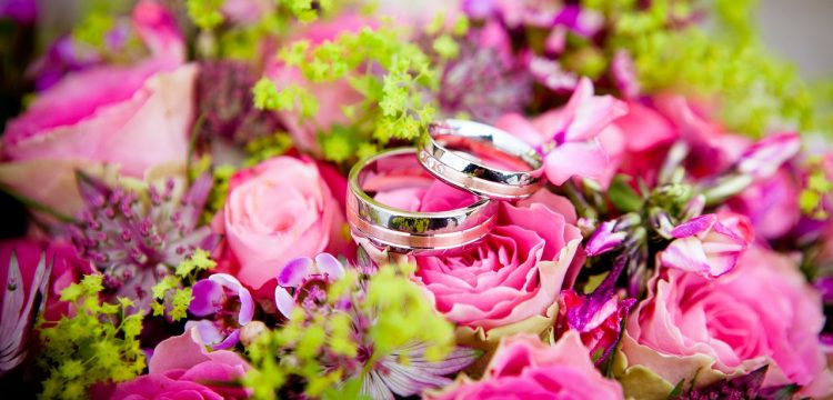 Two wedding bands on top of colorful flowers.